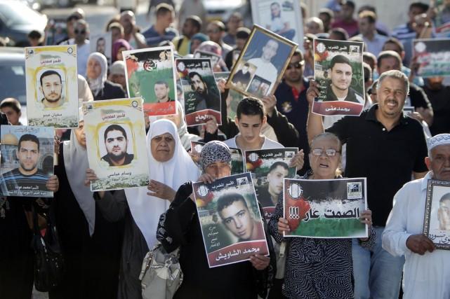 Des militants palestiniens brandissent des photos des détenus... (PHOTO AHMAD GHARABLI, ARCHIVES AFP)