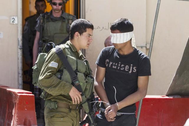 Un soldat israélien escorte un Palestinien arrêté pour... (PHOTO BAZ RATNER, REUTERS)