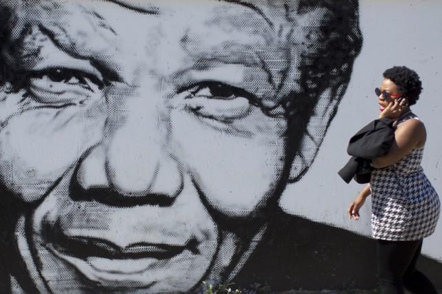 Une femme passe devant une murale à l'effigie... (PHOTO BEN CURTIS, ARCHIVES AP)