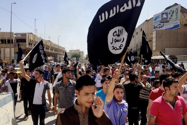 Des partisans de l'EIIL, brandissant des drapeaux d'Al-Qaïda,... (PHOTO ARCHIVES AP)