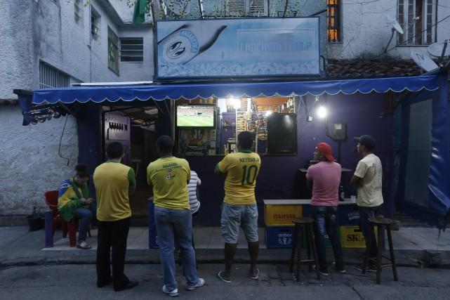 Des amateurs brésiliens regardent un match à la... (Photo Silvia Izquierdo, AP)