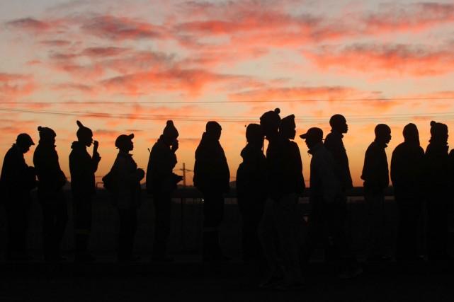 Avant l'aube, une longue file de mineurs chaudement... (PHOTO DENIS FARRELL, AP)