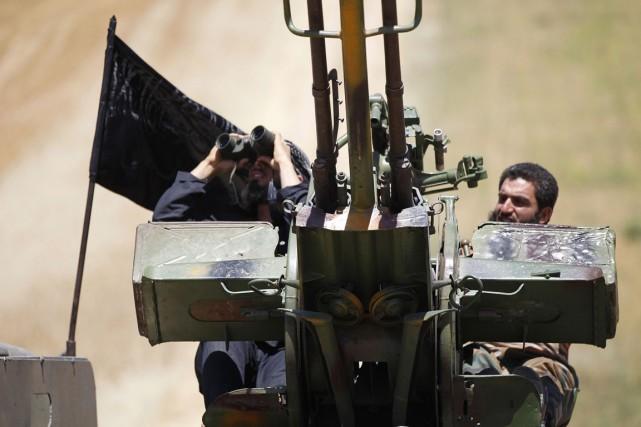 Du haut de leur batterie antiaérienne, deux combattants... (PHOTO HAMID KHATIB, ARCHIVES REUTERS)