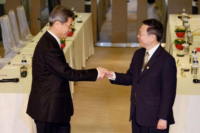Zhang Zhijun (gauche), directeur du Bureau des affaires... (PHOTO SAM YEH, AFP)