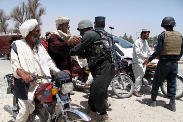 Un policier afghan fouille des civils à un... (PHOTO ABDUL MALIK, AFP)