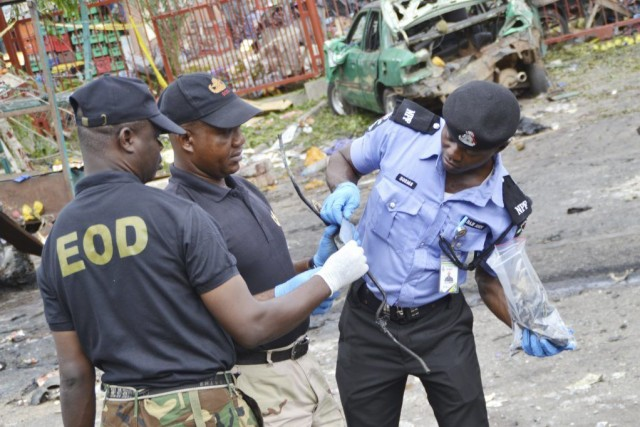 Des experts en explosifs ramassent des indices sur... (Photo AFP)