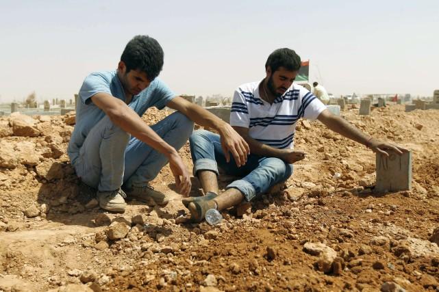 Des Libyens pleurent sur la tombe de la... (Photo ABDULLAH DOMA, Archives AFP)