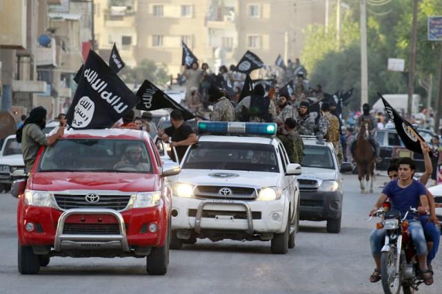 Des militants de l'État islamique paradent dans les... (PHOTO ARCHIVES REUTERS/STRINGER)