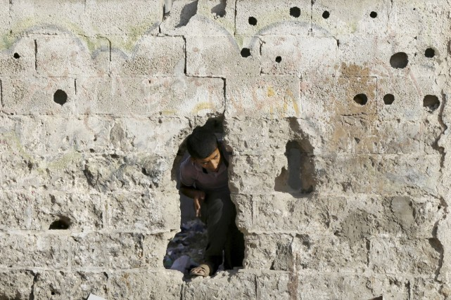 Un garçon palestinien regarde à travers un trou... (PHOTO ADEL HANA, AP)