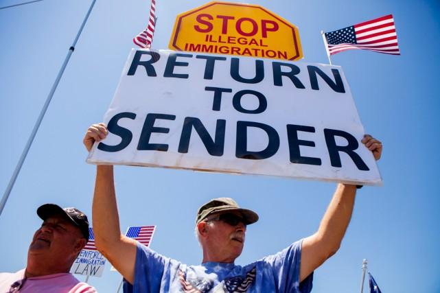 Branissant de pancartes où l'on peut lire «Arrêtons... (Photo Sam Hodgson, Reuters)