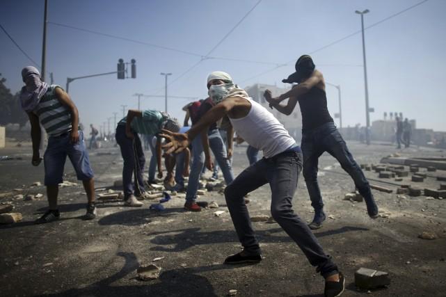 Des Palestiniens masqués lançaient des pierres à des... (PHOTO THOMAS COEX, AFP)