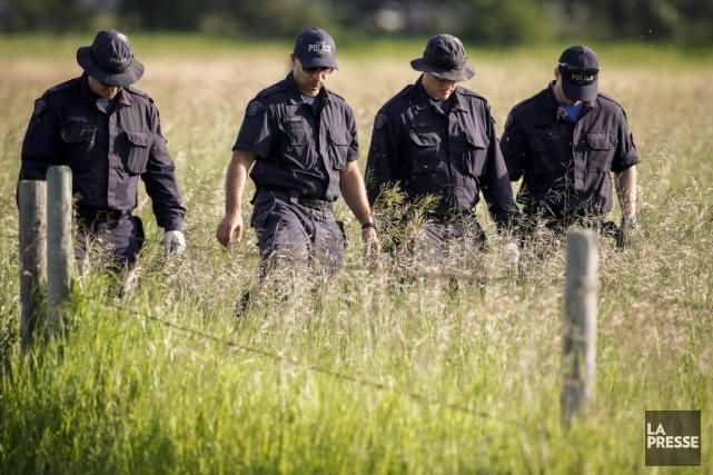 Des policiers participent aux fouilles dans un champ... (PHOTO JEFF MCINTOSH, PC)