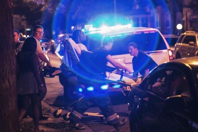 Un homme blessé par balle est transporté sur... (PHOTO AP/SUN-TIMES MEDIA)