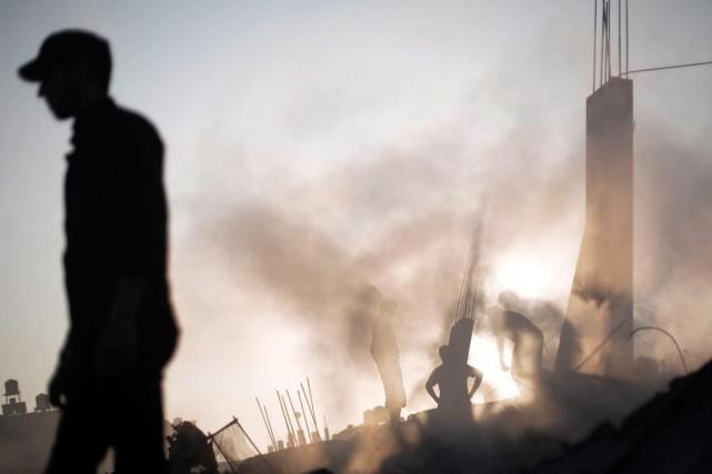 Des Palestiniens examinent les décombres de leur maison... (PHOTO KHALIL HAMRA, AP)