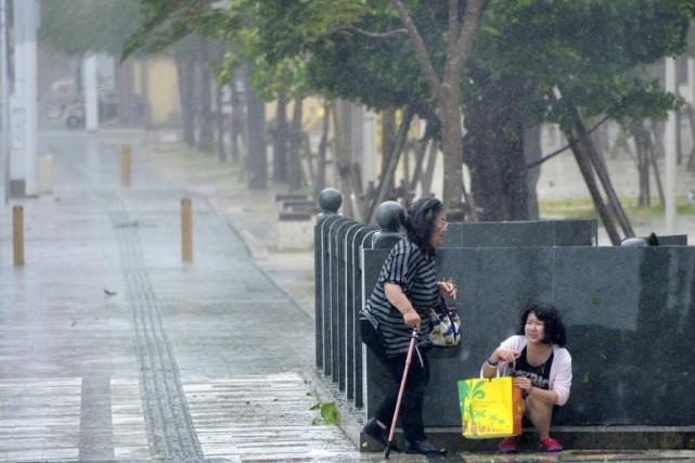 Une jeune femme s'accroupit derrière un muret pour... (PHOTO AFP/JIJI PRESS)