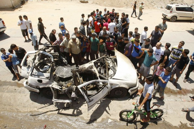 Des Palestiniens s'agglutinent autour de la carcasse d'une... (PHOTO AHMED ZAKOT, REUTERS)