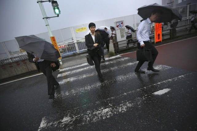 Des piétons bravent les pluies torrentielles et les... (PHOTO EUGENE HOSHIKO, AP)