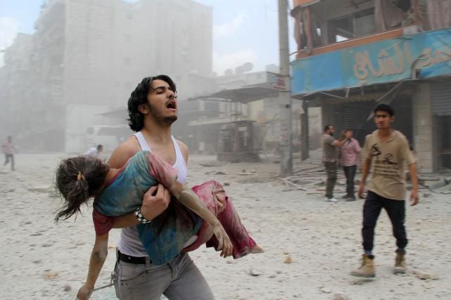 Un homme transporte une jeune fille blessée, lors... (PHOTO BARAA AL-HALABI, ARCHIVES AFP)