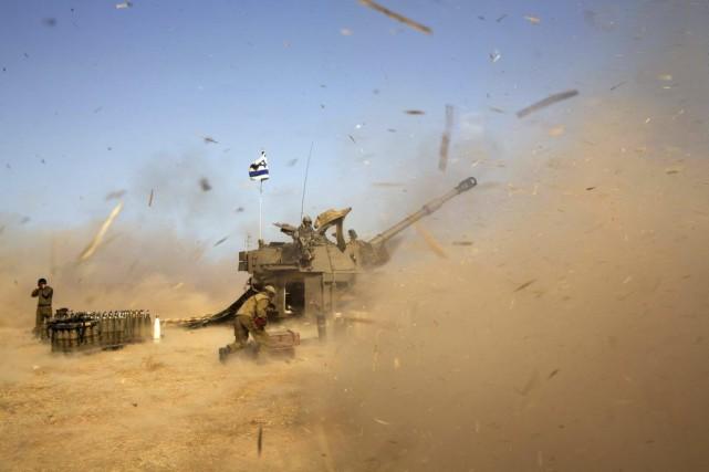 Des Israéliens tirent vers des cibles situées dans... (PHOTO MENAHEM KAHANA, AFP)