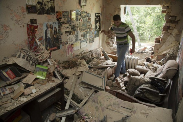 Eugeny Vaschenko entre dans sa maisonendommagée après les... (PHOTO DMITRY LOVETSKY, AP)
