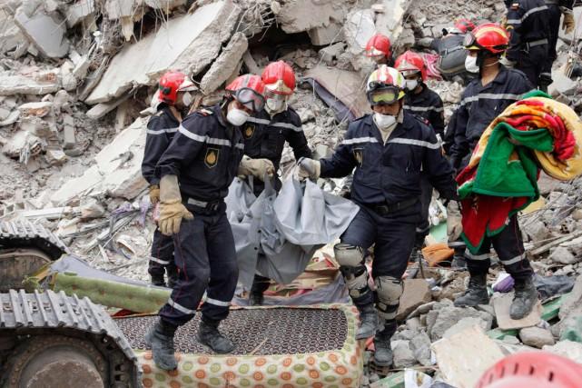 Des pompiers évacuent un corps des décombres d'un... (PHOTO REUTERS)