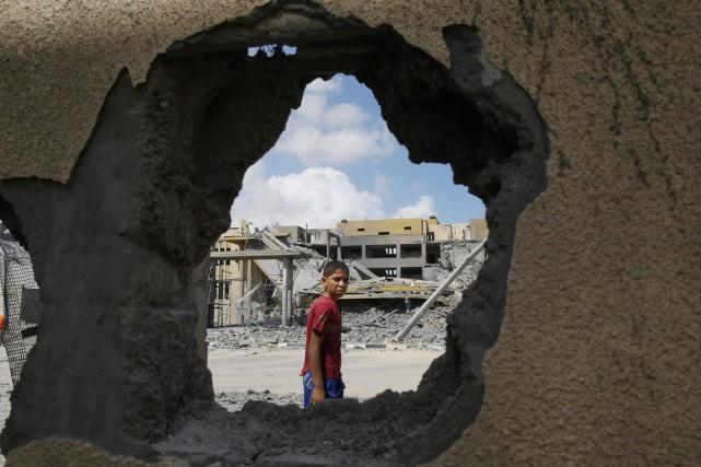 Un garçon passe devant un trou laissé par... (PHOTO LEFTERIS PITARAKIS, AP)