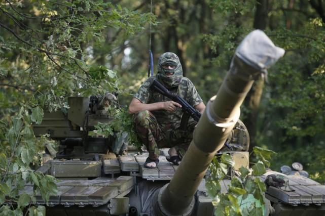 Un séparatiste pro-russe juché sur un char d'assaut... (Photo: Reuters)