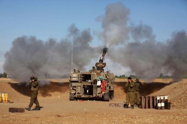 Un tank israélien tire un obus en direction... (PHOTO MENAHEM KAHANA, AFP)