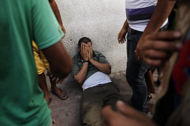 Le père de deux enfants tués jeudi, effondré.... (Photo Reuters)