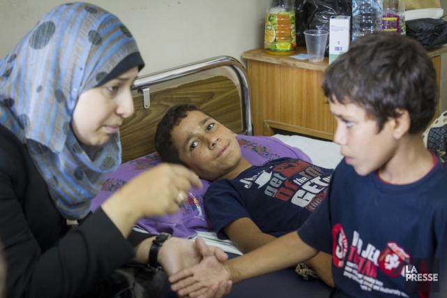 La psychologue Mouira Khalaf prend la main de... (PHOTO OLIVIER PONTBRIAND, LA PRESSE)