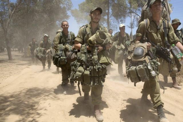 Des soldats israéliens marchent en direction de la... (PHOTO MENAHEM KAHANA, AFP)