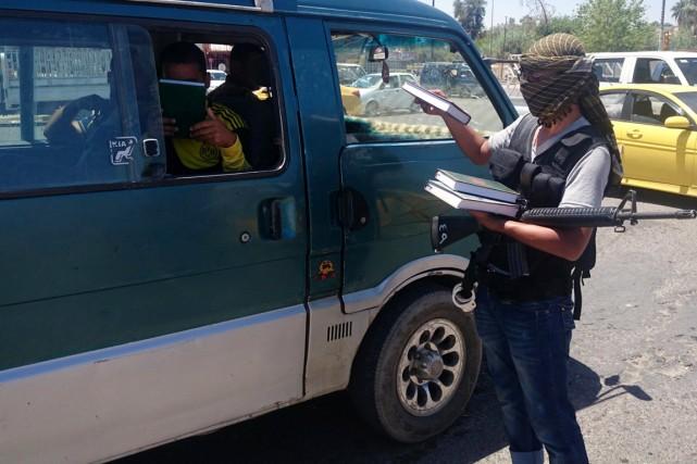 Un combattant de l'EI distribue des exemplaires du... (PHOTO AP)