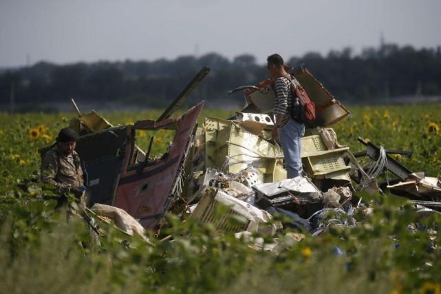 Les débris de l'avion sont inspectés sur les... (Photo Reuters)