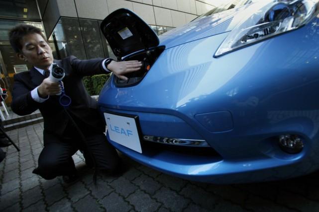 Un employé de Nissan démontre comment brancher la... (Photo archives AP)