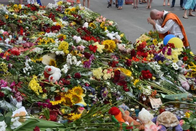 Un moine bouddhiste prie devant des fleurs et... (Photo: AFP)