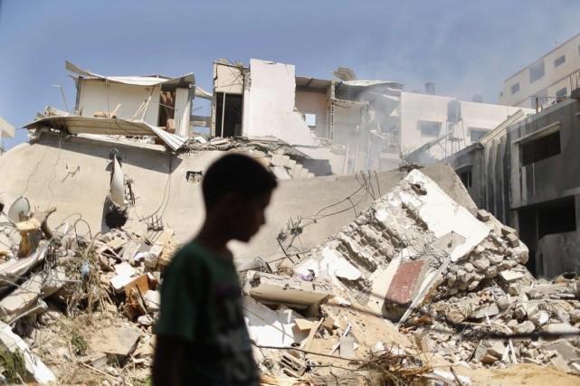 Un garçon palestinien marche devant les ruines de... (PHOTO SUHAIB SALEM, REUTERS)