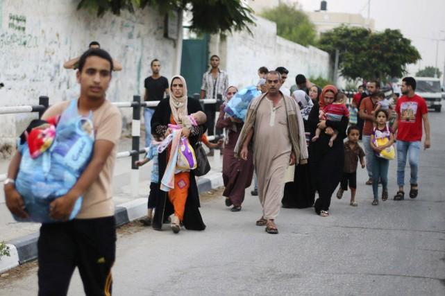 Des Palestiniens fuient leur maison à la suite... (PHOTO IBRAHEEM ABU MUSTAFA, REUTERS)