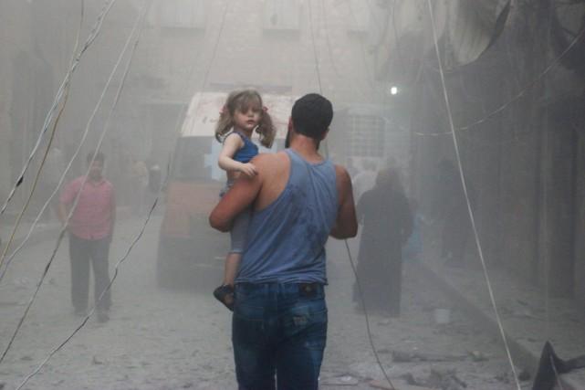 Sa fille dans les bras, un homme marche... (PHOTO BARAA AL-HALABI, ARCHIVES AFP)