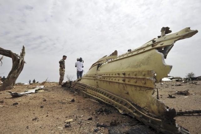 Un soldat et un journaliste regardent les débris... (PHOTO SIA KAMBOU, AFP)