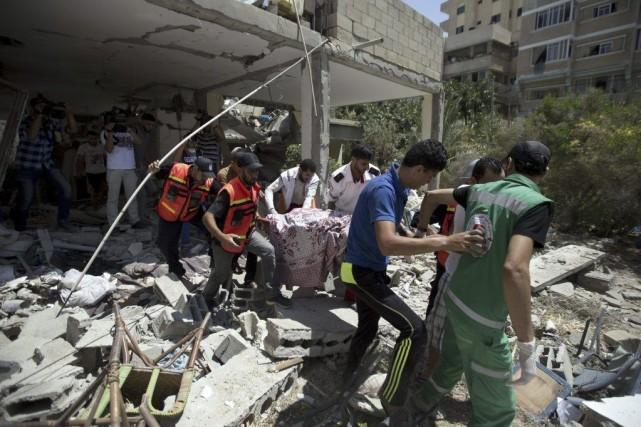 Des secouristes palestiniens transportent le corps d'une femme... (PHOTO MAHMUD HAMS, AFP)