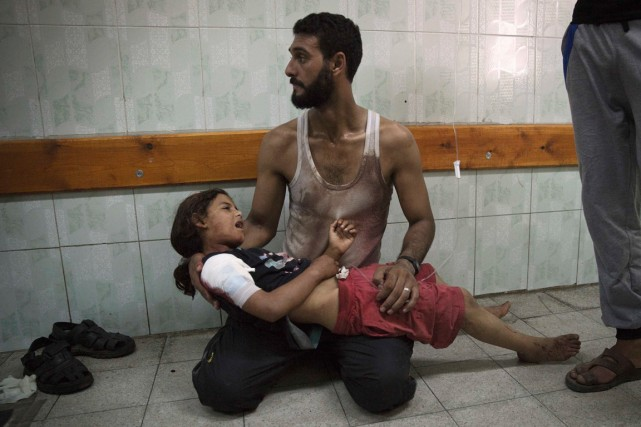 Un Palestinien porte une fillette blessée lors du... (PHOTO FINBARR O'REILLY, ARCHIVES REUTERS)