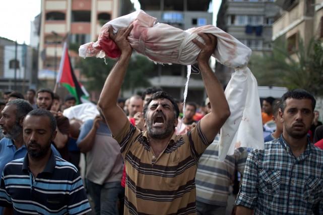 Un Palestinien porte le corps d'un enfant mort... (PHOTO MAHMUD HAMS, AGENCE FRANCE-PRESSE)
