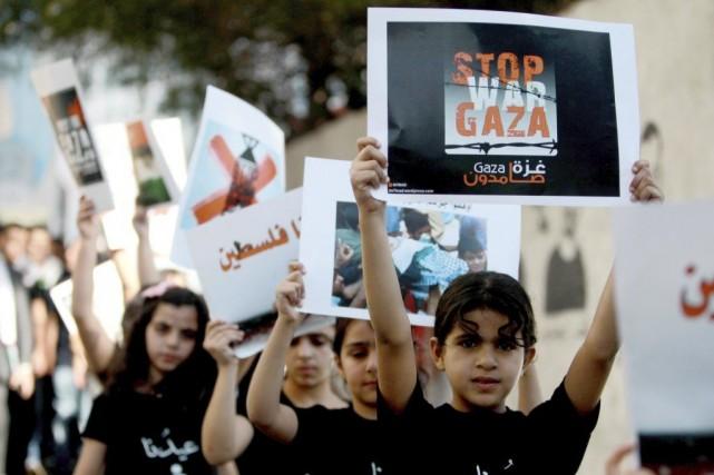 De jeunes Palestiniens tiennent des pancartes où il... (PHOTO MUSA AL-SHAER, AFP)