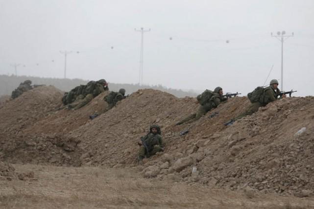 Dss soldats israéliens en poste lundiprès du kibboutz... (Photo: Reuters)