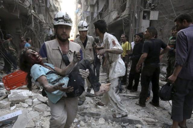 Un secouriste transporte une jeune fille blessée par... (PHOTO ZEIN AL-RIFAI, AFP)