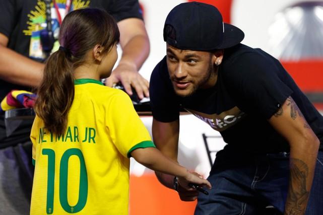 L'attaquant brésilien Neymar a salué une jeune fan... (Photo Yuya Shino, Reuters)