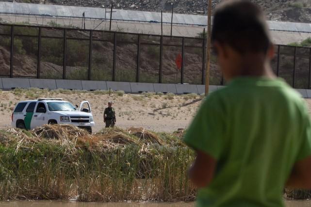 Un enfant mexicain regarde unpolicier assigné à la... (Photo Jesus Alacazar, archives AFP)