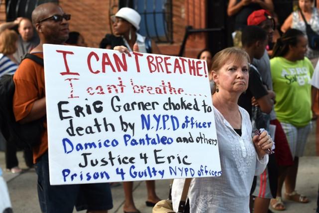 Une manifestante brandit une affiche critiquant la police... (Archives Reuters)