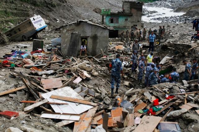 Des sauveteurs cherchent des survivants ensevelis à Mankha.... (Photo Niranjan Shrestha, Associated Press)