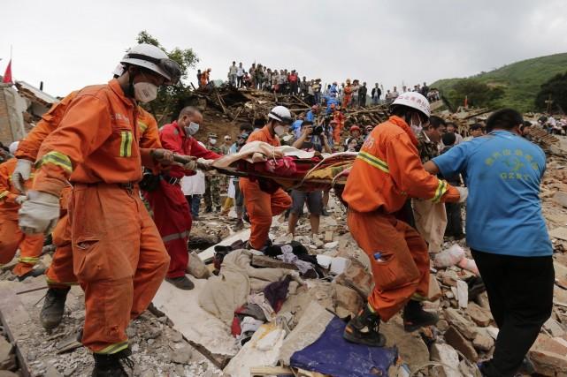 Des secouristes sortent un corps des décombres après... (Photo Andy Wong, AP)